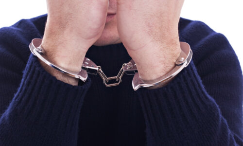 Arms on the face, with a handcuffs on the hands